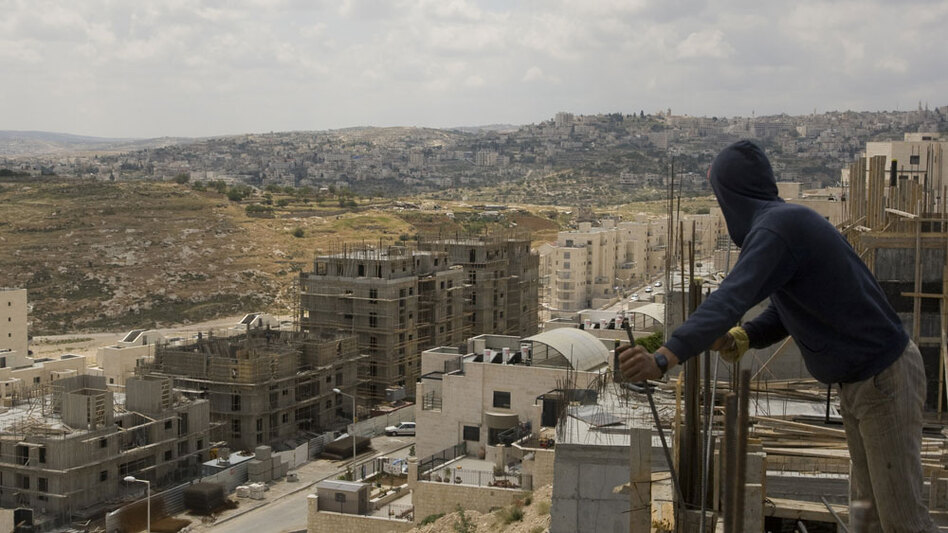 Palestinian laborers work on a new housing project at the Israeli settlement of Har Homa in East Jerusalem.