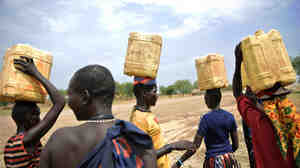 South Sudanese women carry cans filled with water on their heads at Terekeka, north of Juba.