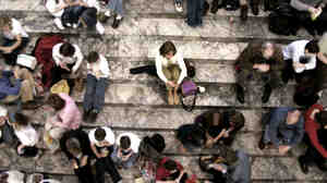 A woman sits alone atop crowded outdoor stairs.