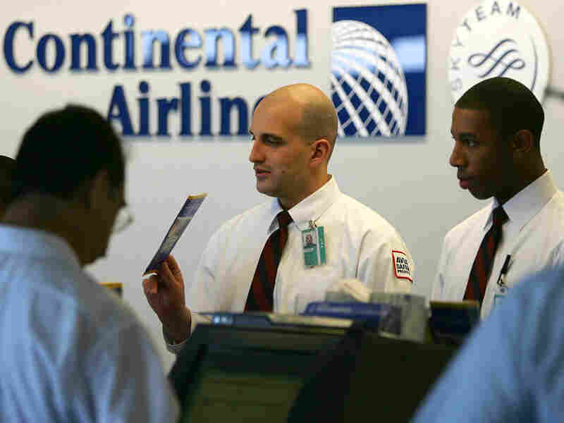 Continental Airlines agents help passengers with ticketing at Los Angeles International Airport.