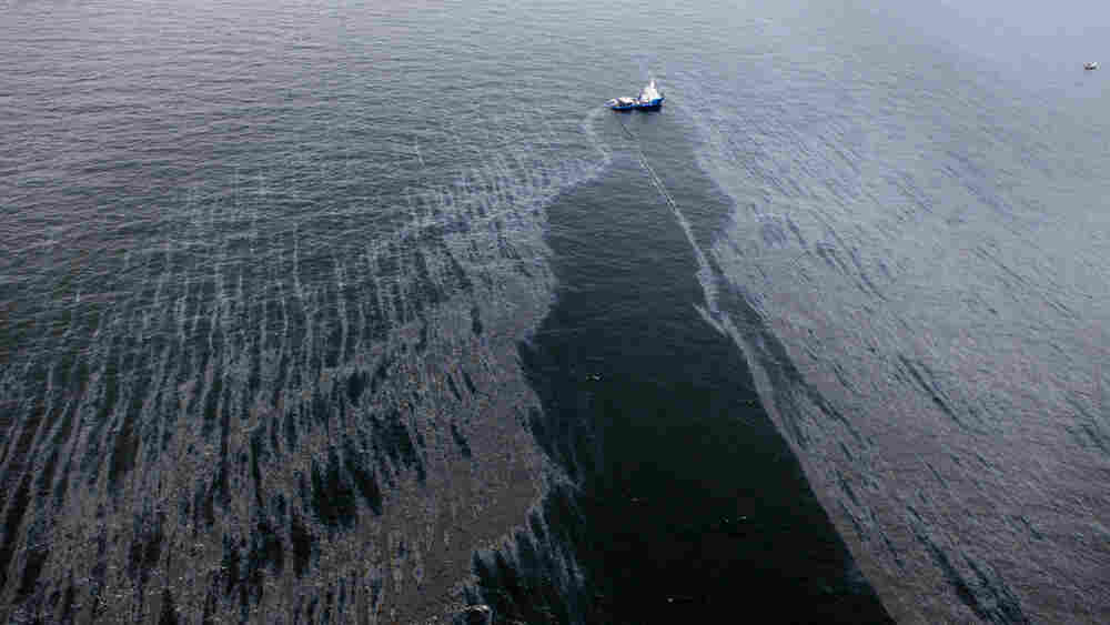 A boat with an oil boom tries to contain the spill in the Gulf.