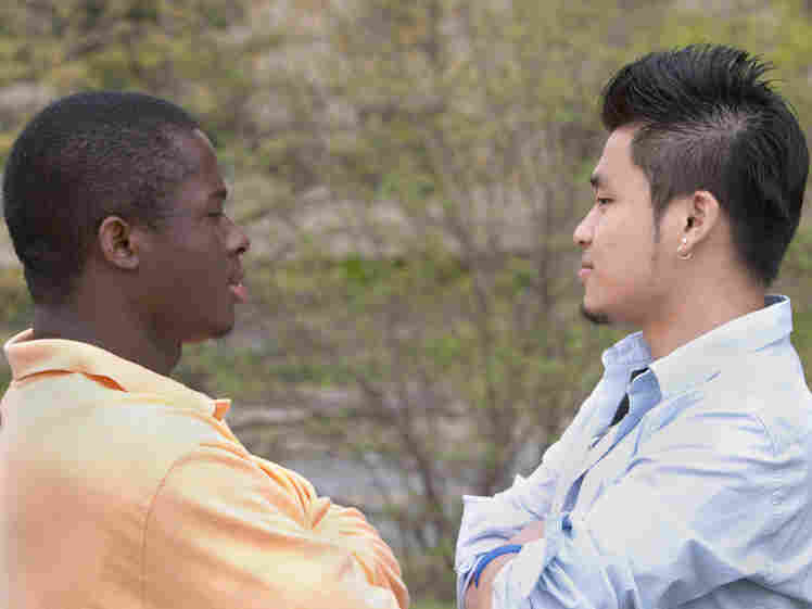 Two men, one black and one Asian, stare at each other
