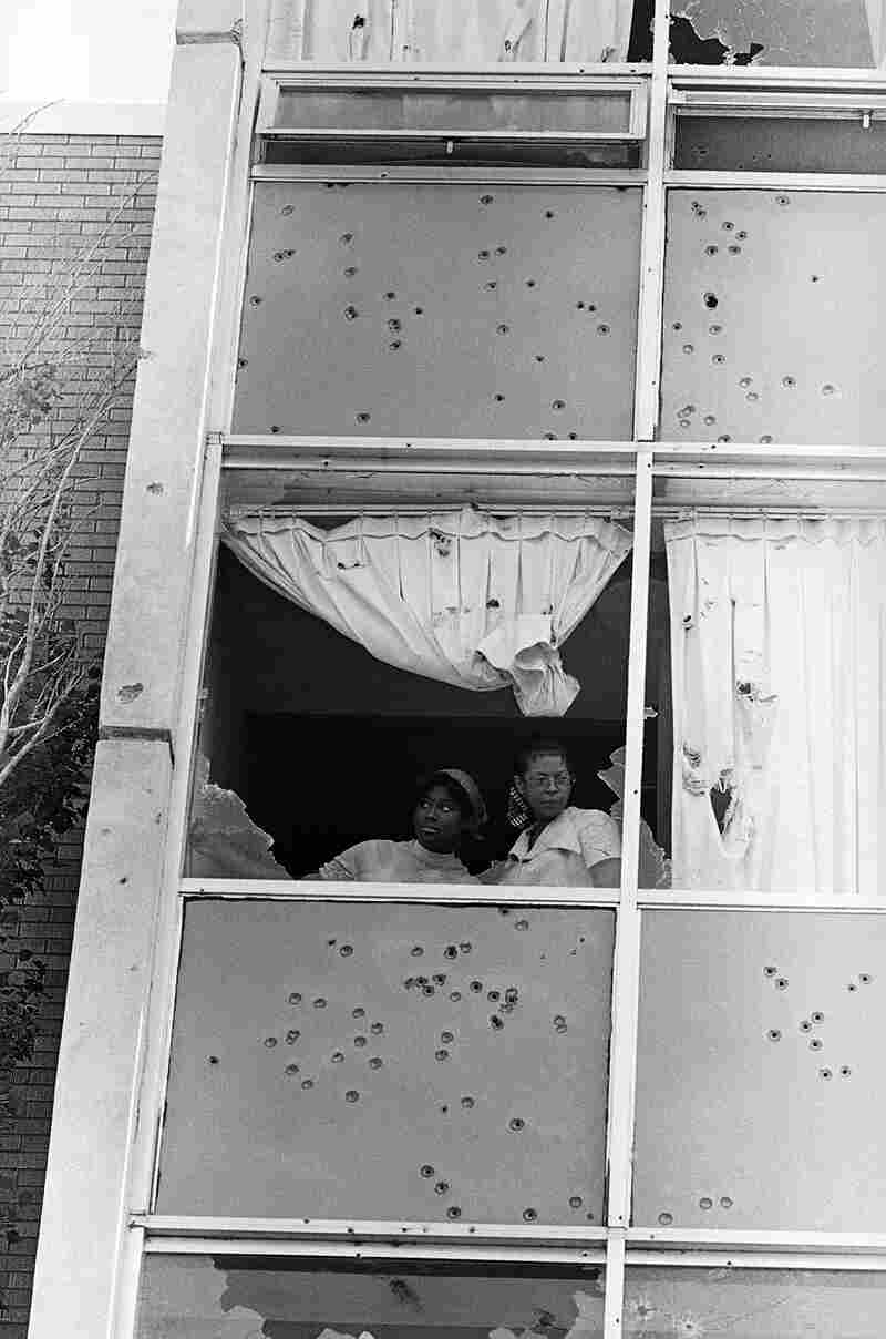 Two students at Jackson State College peer from a window that was shot out by police on campus.