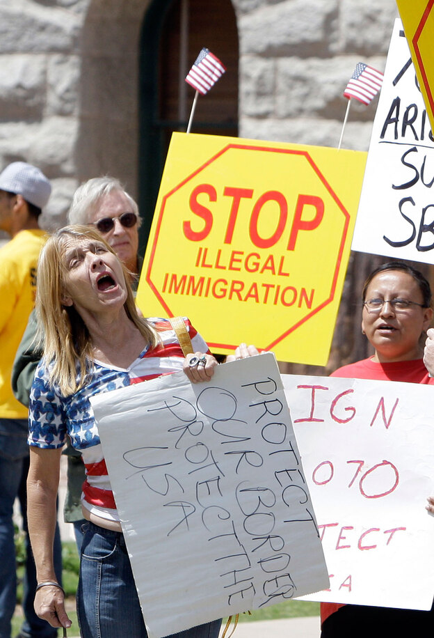 Supporters of Arizona's immigration bill rally April 23 at the state capitol in Phoenix as Gov. Jan Brewer prepared to sign the measure into law.