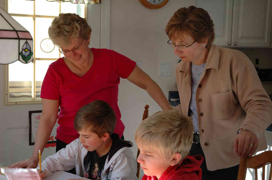 Kathy Bush and Mary Ritchie help their sons with homework.