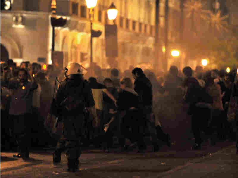 Riot police use pepper spray against demonstrators outside the Greek parliament building in Athens