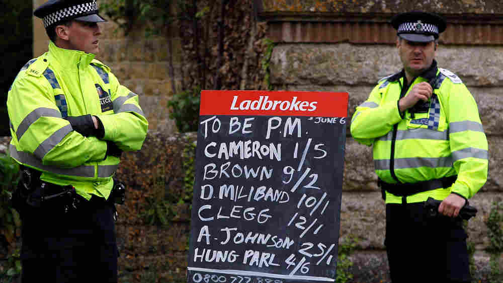 Policemen stand near a board showing betting odds on election results in Witney, England.