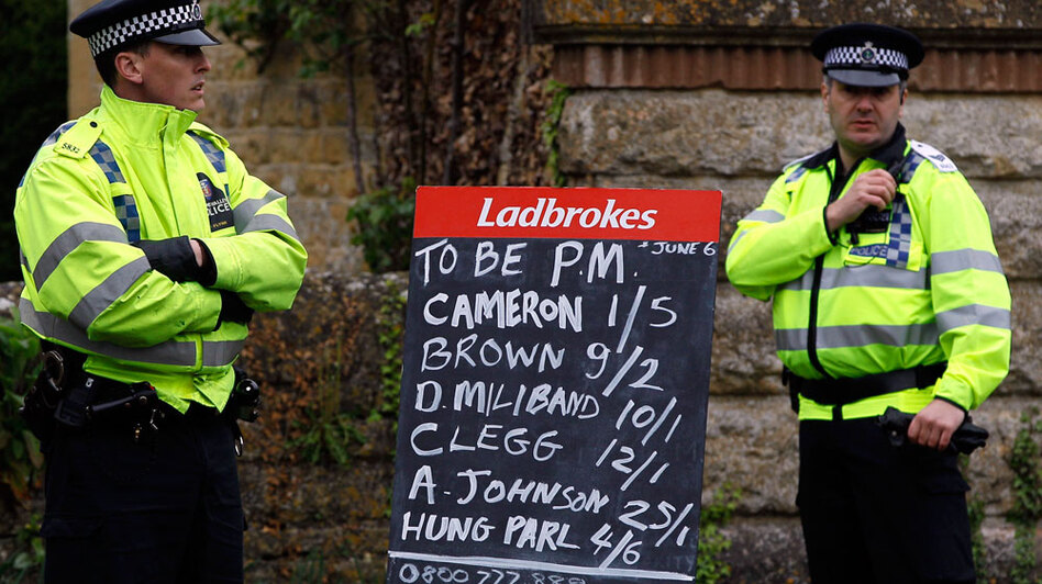 Policemen stand near a bookmaker's board showing the betting odds on the general election result near a polling station Thursday in Witney, England. Odds were 4/6 for a hung Parliament.