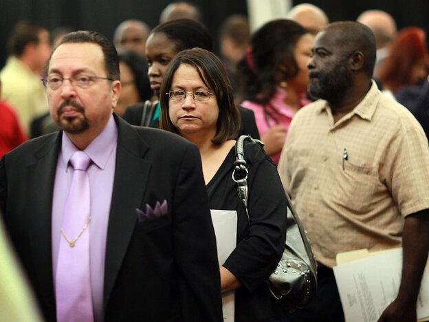 People attend a job fair April 22 in Davie, Fla.