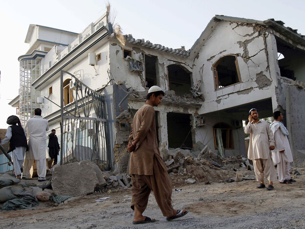 Afghans walk by a house destroyed in a suicide bombing the previous night in Kandahar last month. Fear has gripped the southern city ahead of an upcoming U.S. offensive, as Taliban militants flood into the area in preparation.