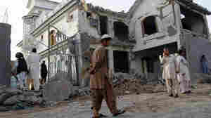 Afghans walk by a house destroyed in a suicide bombing the previous night in Kandahar,