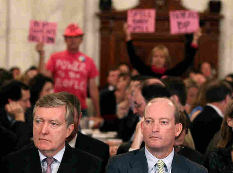 BP America's Lamar McKay and Executive Vice President David Nagel wait to testify as people protest.