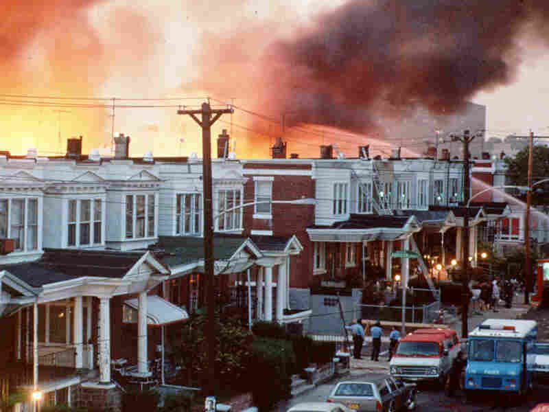 File photo shows Philadelphia row houses burning after officials dropped a bomb on the MOVE house.