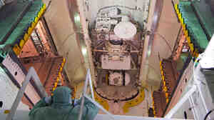 A technician performs a final check of space shuttle Atlantis' payload bay doors.