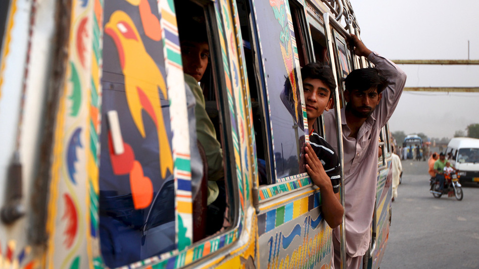 Young men ride a bus home after watching the military spectacle of the Wagah border ceremony.