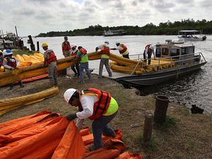 Contract workers load oil booms onto a boat to protect marshlands 