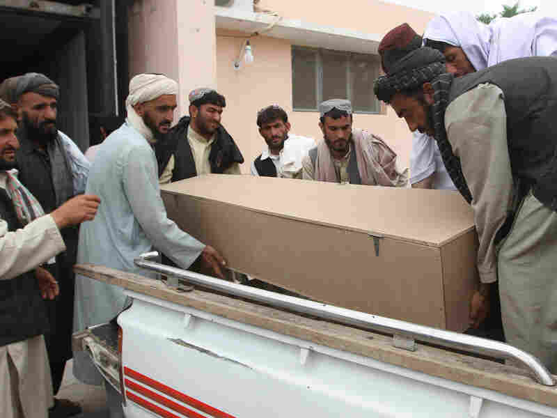 Paramedics and Afghan civilians carry a coffin containing the body of one of five people.