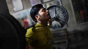 Muhammad Yasir, 23, lifts free weights at Gold's Gym in Gujranwala, Pakistan.