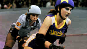 Skaters from the Tough Cookies (in blue) and the Varsity Brawlers (purple) are seen in action.