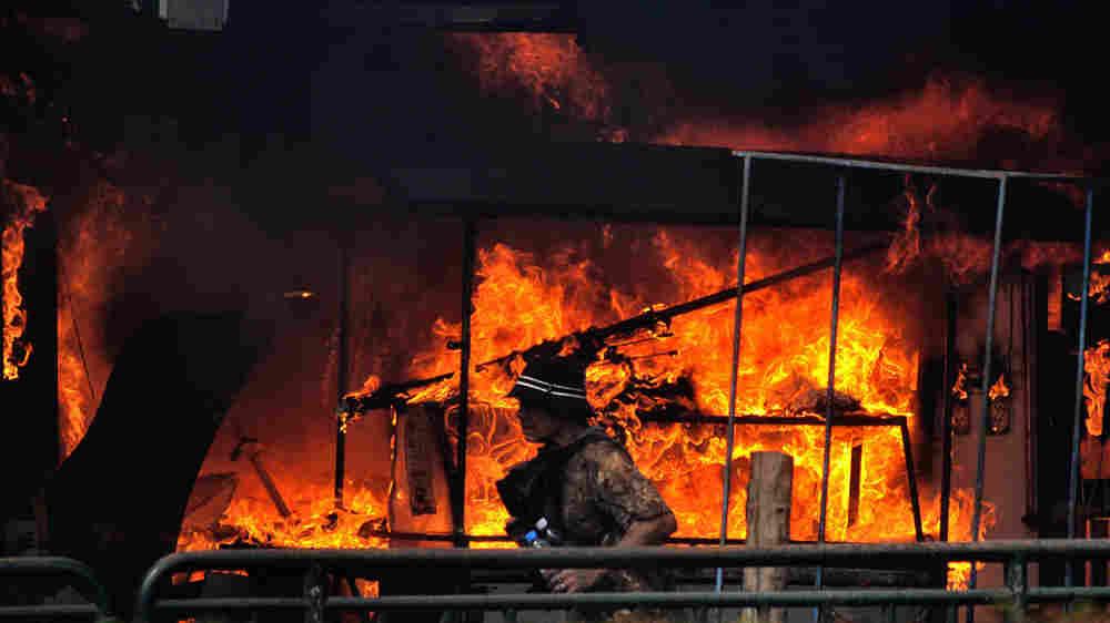 Anti-government protester runs beside a shop set ablaze