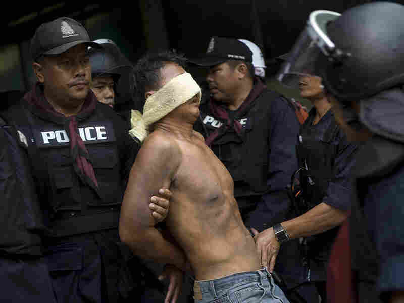 A Red Shirt protester is detained by Thai policemen