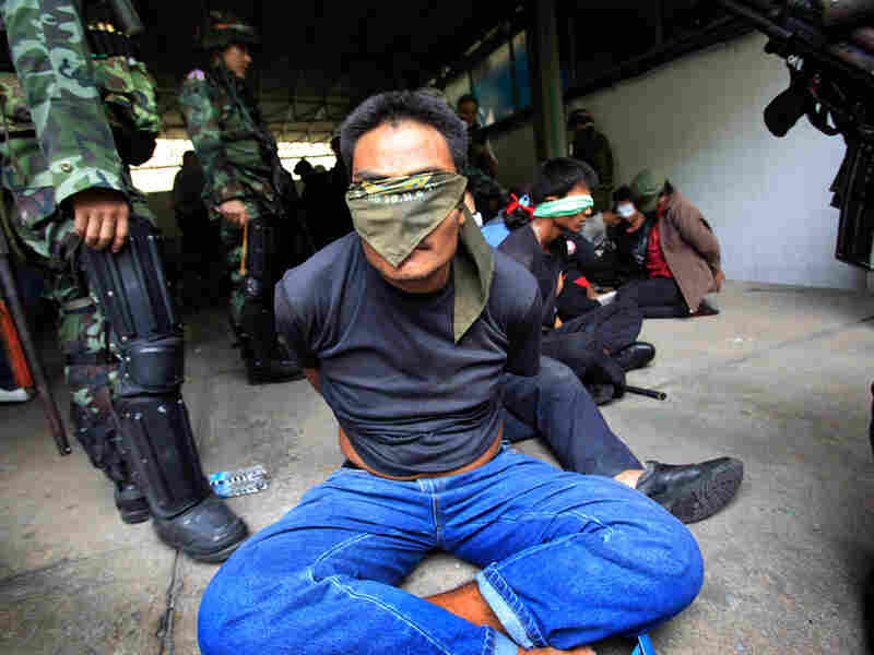 Anti-government protesters are held by Thai soldiers