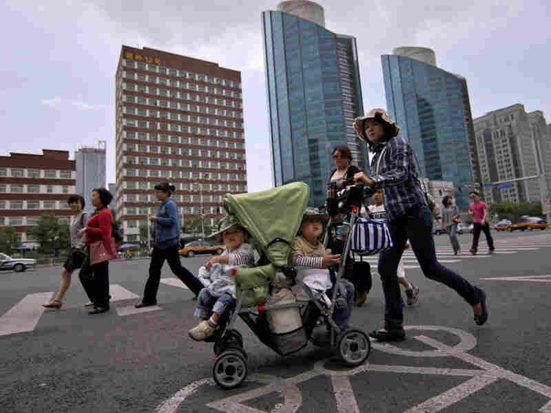 A woman pushes a stroller in Beijing.