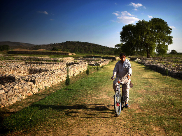A man rides his bike down the former main street of the ancient city of Sirkap, which was a crowded settlement more than 2,000 years ago. Villagers now use the street as a shortcut home.