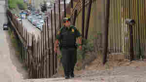 A U.S. Border Patrol officers walks beside the fence that divides the U.S. from Mexico.