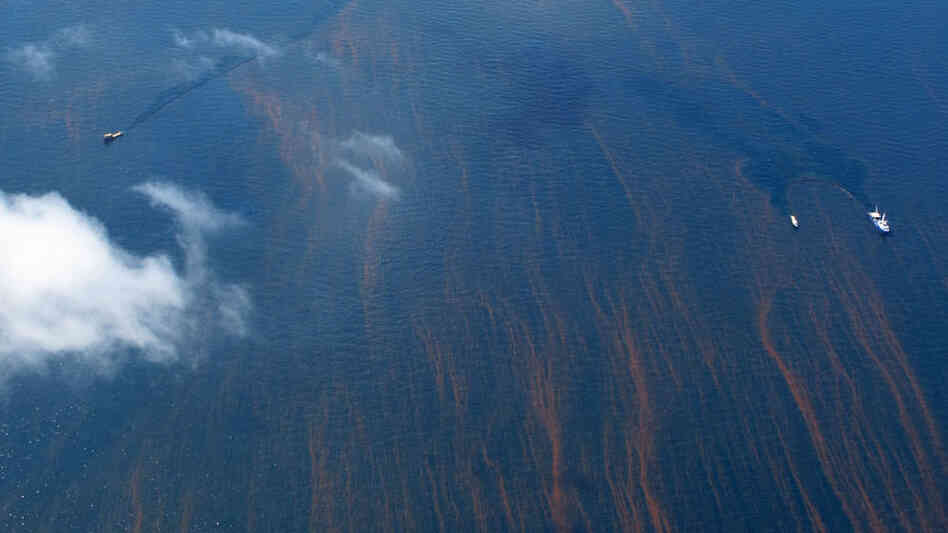 The Gulf's blue waters are streaked with reddish tendrils of oil. Debbie Elliott/NPR