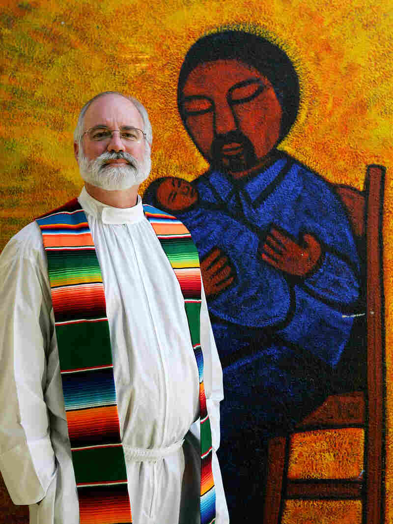The Rev. Gregory Boyle in front of a mural painted by artist Jose Ramirez.
