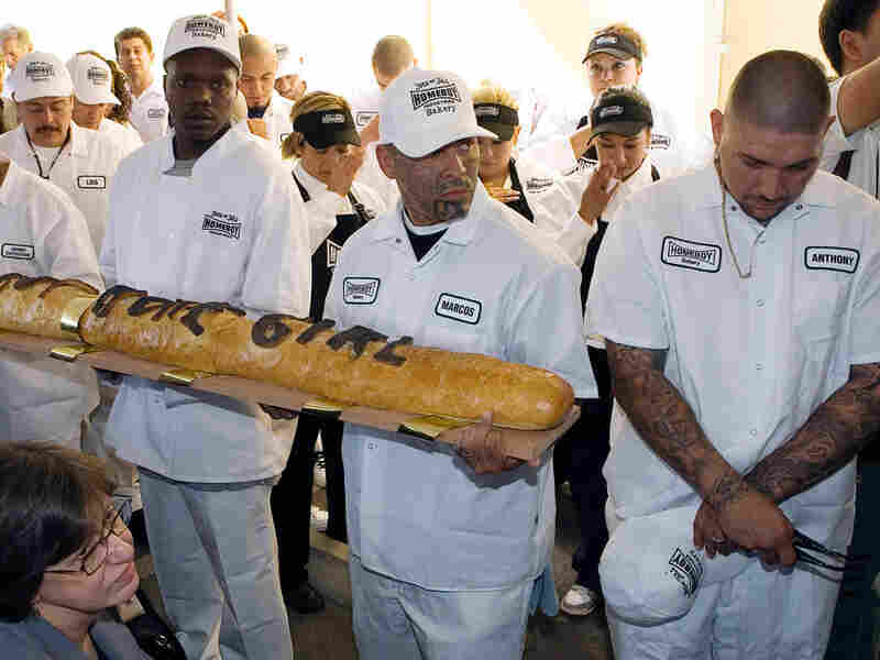 Homeboy Industries Bakery workers hold a giant loaf of bread.