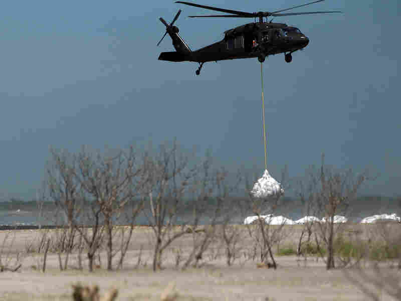 A Louisiana National Guard helicopter airlifts sandbags