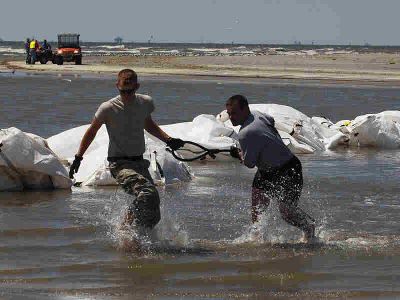 Louisiana National Guard members retrieve a cable attached to sand bags.