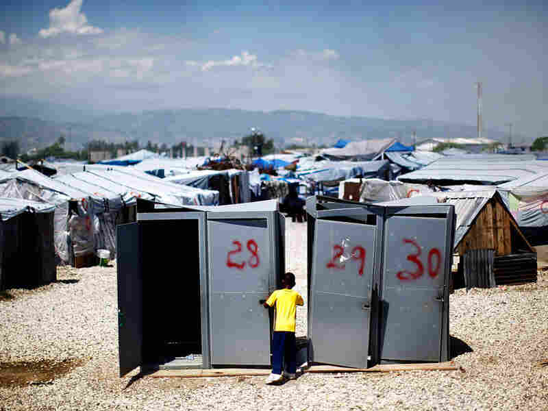 A little boy plays near four unused portable toilets