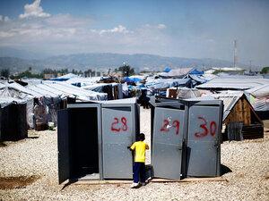 A little boy plays near four unused portable toilets
