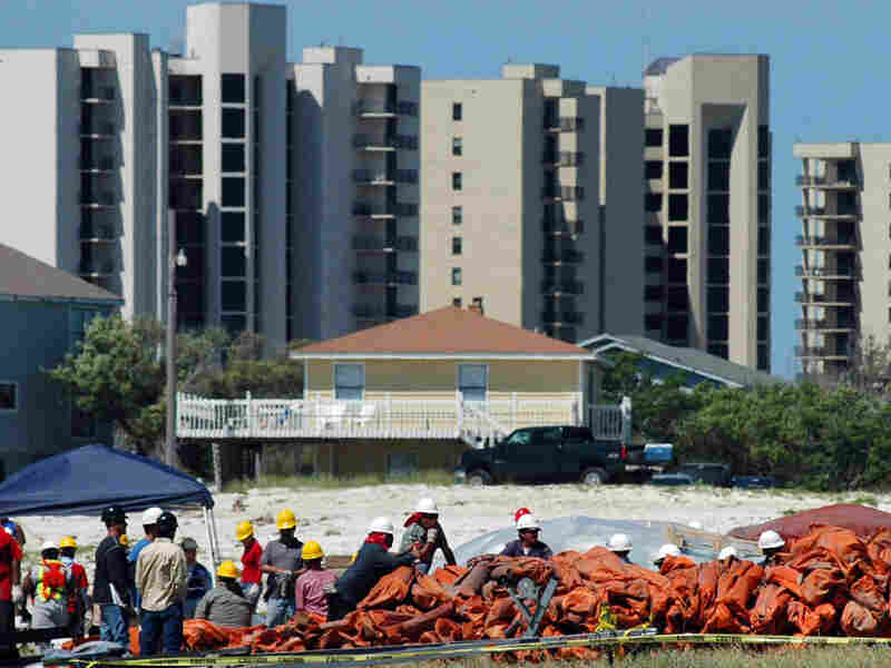 Workers handle oil-blocking booms in Alabama with condominiums in the background