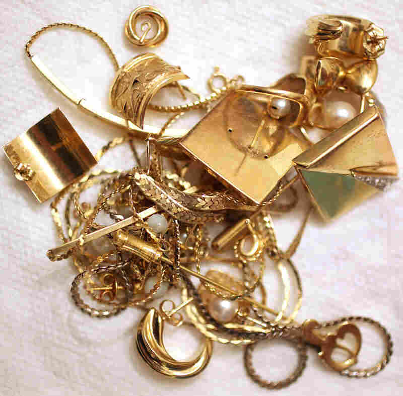 Gold jewelry pieces sit in a pile.