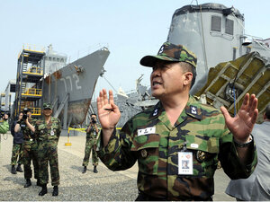 South Korean officer with wreckage of ship
