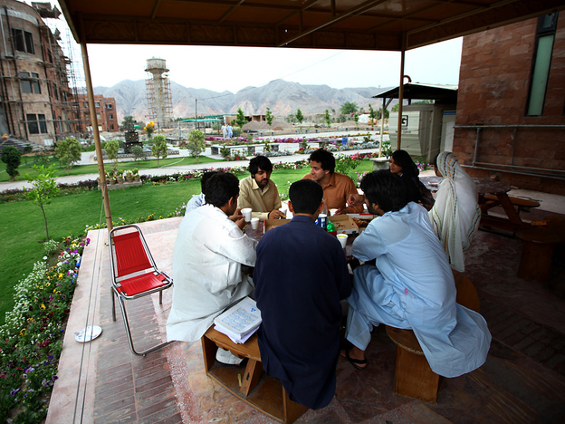 <strong>Sharing A Pizza:</strong> Students chat in an outdoor cafe on the campus of the Institute of Management Sciences. In the background are the mountainous tribal areas of the former Northwest Frontier province.