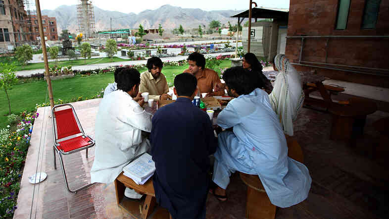 Students chat in an outdoor cafe on the campus of the Institute of Management Sciences.