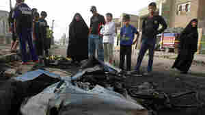 Iraqis inspect the damage at the site of a car bomb blast