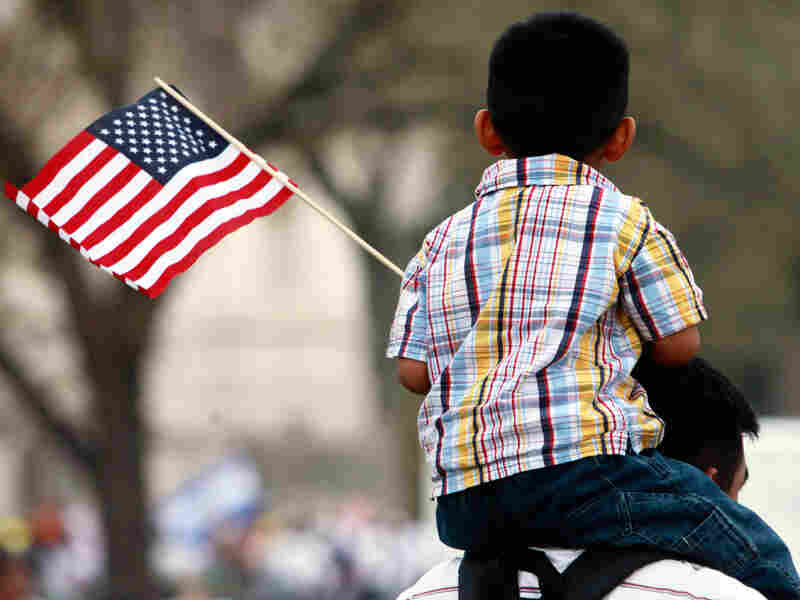 A child waving an American flag sits on an adult's shoulders.