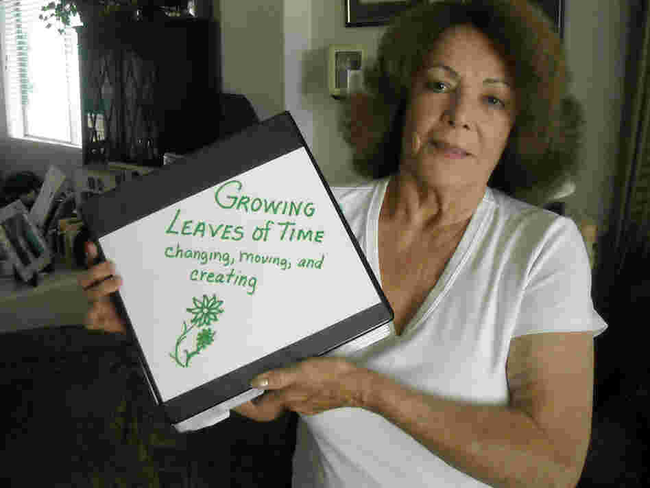 Mary Marin holds a scrapbook of photos from her childhood in a South Phoenix barrio.