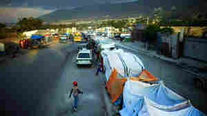 Haiti quake survivors set up camp on busy road median south of Port-au-Prince