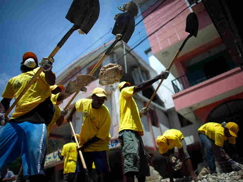 Haitians help remove rubble in the coastal city of Leogane