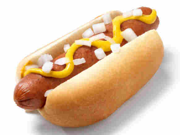 a hot dog with mustard and onions