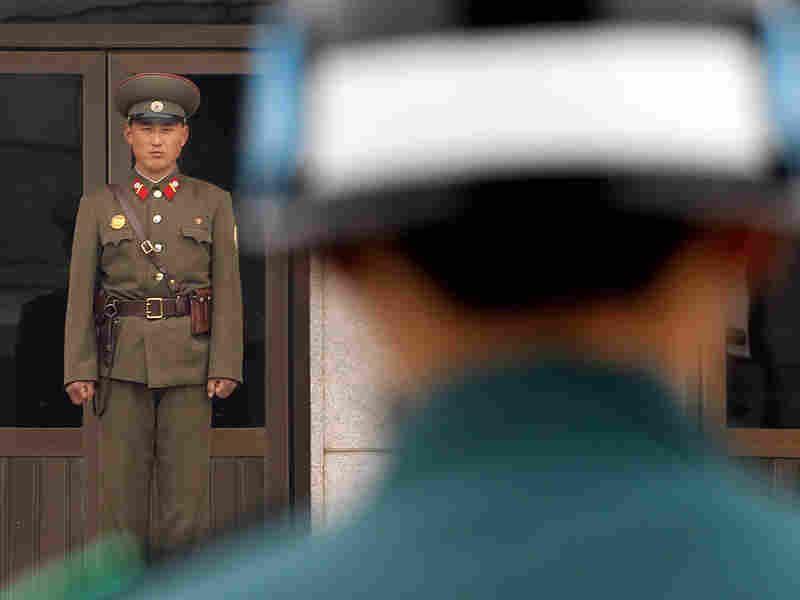 A North Korean soldier (left) and a South Korean soldier stand opposite each other at the DMZ.