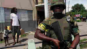 Soldier patrols while resident of Tivoli Gardens neighborhood in Kingston looks on