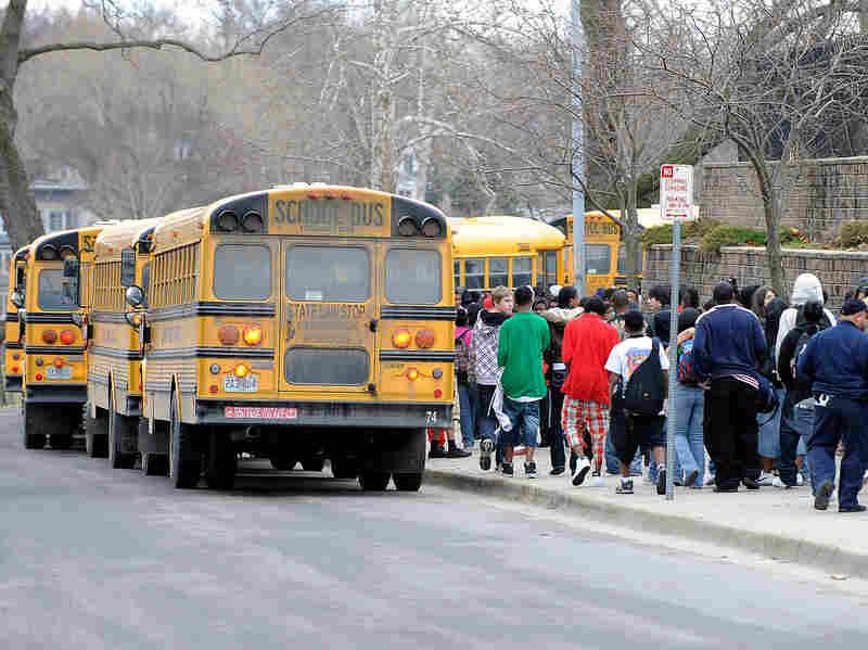 Students walk in line towards school buses